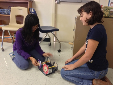 Two students try to figure out why their rubber-band car isn't working.
