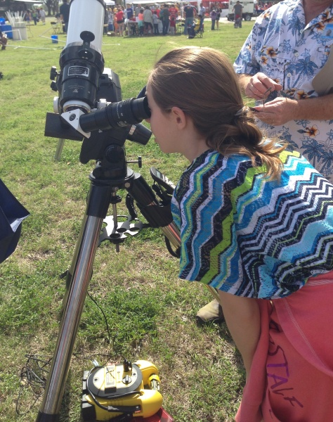 My daughter peers through a telescope at the sun during the Girls Inc Science Festival